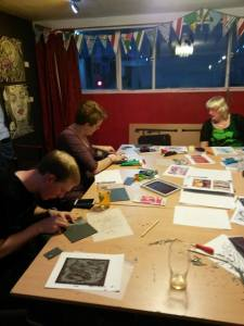 Folks linocutting dragons at a workshop with Caroline Misslebrook